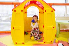 A small cheerful girl sits in a plastic toy house for children and holds several colorful balls in her hands. A yellow colored hou. Se with a red roof is in the stock images