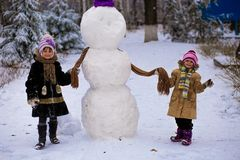 A small cheerful girls put on a scarf for a big snowman. A cute little sisters has fun in winter park, wintertime Royalty Free Stock Photography