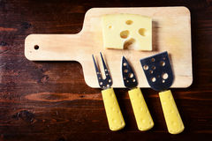 Small cheese knives  and chopping board with emmenthal cheese on. Dark wooden table top view Stock Photography