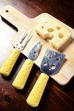 Small cheese knives  and chopping board with emmenthal cheese on. Dark wooden table top view Stock Photos