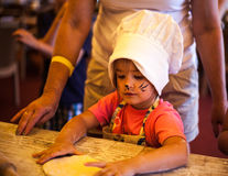 Small chef girl cooking homemade bread with grandma on kitchen. Small cute kid in a kitchen with a face art cat cooking homemade bread royalty free stock photography