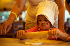 Small chef girl cooking homemade bread, using rolling pin with grandma on kitchen. Small cute kid in a kitchen with a face art cat cooking homemade bread stock photo
