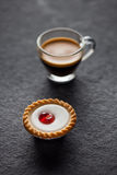 Small cherry cake with a glass of fresh espresso Stock Photography