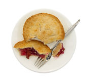 Small cherry pie pieces on plate with fork top view Royalty Free Stock Photos