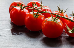 Small cherry tomatoes on black stone background. Closeup, selective focus Royalty Free Stock Photos