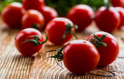 Small cherry tomatoes on wooden background. Selective focus Stock Photos