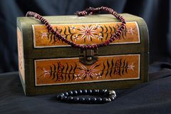 Small chest with old school painted ornaments and beaded necklace. Small chest with  old school painted ornaments and beaded necklace stock photos