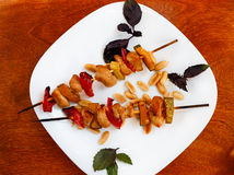 Small chicken kebabs with paper and zucchini. On white plate on wooden table Stock Photography