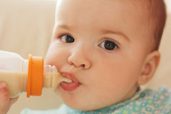 Small child. The little girl eats from a bottle Stock Photography
