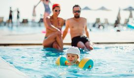 A small child with armbands and parents in swimming pool on summer holiday. A small toddler child with armbands and parents in swimming pool on summer holiday royalty free stock images