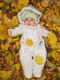Small child in autumn yellow leaves. A small child in a warm jumpsuit lies in autumn yellow leaves Stock Images