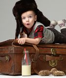 Small child baby boy in winter hat lying on retro leather travel bag in winter snow hat  with bottle of milk. Christmas concept on grey background Royalty Free Stock Image