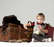 Small child baby boy in winter hat sitting near retro leather travel bag in winter snow hat  drinking bottle of mil. K. Christmas concept on grey background Stock Photos