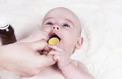 Small child, a baby at the doctor`s office and he is given a medicine for coughing and allergies from a spoon. A very small child, a baby at the doctor`s office stock image