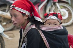 A small child in a bag behind a teenage girl. Red dzao - a small nation of North Vietnam stock images