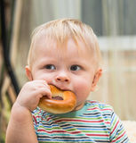 Small child with a bagel Stock Images