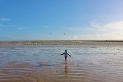 Small child on the beach with kitesurfers in the distance Royalty Free Stock Images