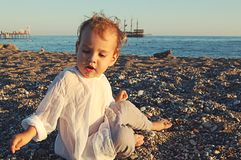 Small child on the beach on the sand in Side, Turkey. Against the sea stock images