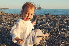 Small child on the beach on the sand in Side, Turkey. Against the sea royalty free stock photos