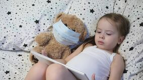 A small child with a bear in a mask plays a tablet while lying on the bed. Kovid-19. Kid is quarantined at home