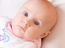 Small child with big blue eyes. Small lying child with big blue eyes Royalty Free Stock Images