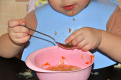 Small child in blue bib explores food in spoon during meal Royalty Free Stock Images