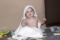 Small child with blue eyes sitting with towel after bathing and. Smiling happily royalty free stock photos