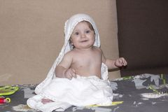 Small child with blue eyes sitting with towel after bathing and. Smiling happily stock photos
