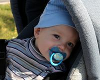 A small child in a stroller with a pacifier smiling royalty free stock images