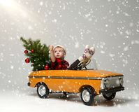 Small child boy in winter sitting in a yellow retro toy car pulls on Christmas tree decorated. On heavy snow background stock photo
