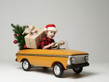 Small child boy in winter sitting in a yellow retro toy car pulls on Christmas tree decorated. On grey background royalty free stock image