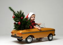 Small child boy in winter sitting in a yellow retro toy car pulls on Christmas tree decorated. On grey background stock images