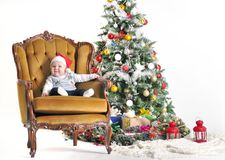 Small child in a cap Claus's sonata sits in chairs about a Christmas tree Stock Image