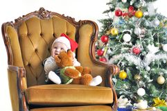 Small child in a cap Claus's sonata and teddy bear sits in chairs about a Christmas tree Royalty Free Stock Photo