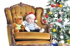 Small child in a cap Claus's sonata and teddy bear sits in chairs about a Christmas tree Royalty Free Stock Images