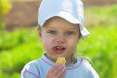 Small child in a cap eating cookies Royalty Free Stock Image