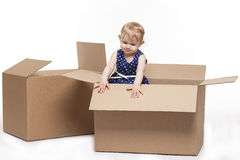 A small child in cardboard boxes stock photo