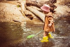 Small child catches fish and frogs in the river royalty free stock photography