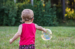 Small Child Chasing Bubbles Royalty Free Stock Photography