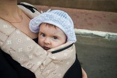 A small child in a children`s backpack with mom. Half a year old baby. Walk down the street. stock image