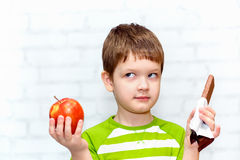 Small child chooses chocolate or apple. On a light background in the studio stock photos