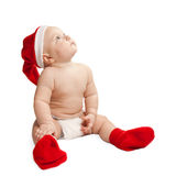 A small child in a Christmas hat and boots Stock Image