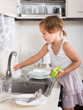 Small child cleaning dishes Stock Image