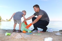 A small child collects trash on the beach. His dad points his finger where to throw garbage. Parents teach children cleanliness. Clean planet concept. A small stock image
