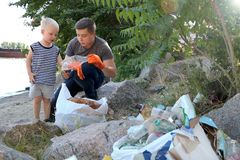 A small child collects trash on the beach. His dad points his finger where to throw garbage. Parents teach children cleanliness. Clean planet concept. A small royalty free stock photo