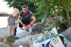 A small child collects trash on the beach. His dad points his finger where to throw garbage. Parents teach children cleanliness. Clean planet concept. A small stock photo