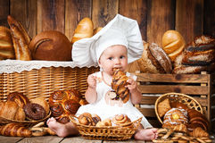 Small child cooks a croissant in the background of baskets with rolls and bread. Royalty Free Stock Images