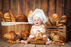 Small child cooks a croissant in the background of baskets with rolls and bread. Small child cooks a croissant in the background of baskets with rolls and bread Stock Image
