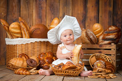 Small child cooks a croissant in the background of baskets with rolls and bread. Small child cooks a croissant in the background of baskets with rolls and bread royalty free stock photography