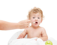 Small child with curly hair, the mother feeds with spoon Royalty Free Stock Photography